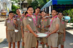 Chiang Mai, Thailand: Boy Scouts at Thai Temple. A troop of Thai Boy Scouts wearing their uniforms and pink kerchiefs carrying a bowl of food to the monks' royalty free stock images
