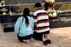 Chiang Mai, Thailand: Devout Thais Praying at Wat Suan Dok. Chiang Mai, Thailand: Two devout barefooted Thais kneel in prayer at an outdoor shrine at Wat Suan royalty free stock photos
