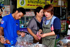 Chiang Mai, Thailand: Food Vendors at Marketplace. Three Thais preparing food at their stand selling meats at the Chiang Mai Gate Food Market in Chiang Mai Royalty Free Stock Images