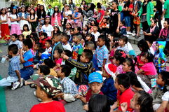 Chiang Mai, Thailand: Group of Children in Schoolyard. A rapt audience of young school children watching a performance during an outdoor assembly at their school Royalty Free Stock Photos