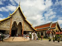 A temple in Chiang Mai. Chiang Mai, Thailand - July 31, 2017: a sacred temple in Chiang mai in a cloudy day. People walking in front stock photos