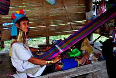 Chiang Mai, Thailand: Long Neck Woman Weaving. Hill tribe long neck Thai woman wearing multiple golden rings around her neck weaving with a hand loom at the Baan Stock Images