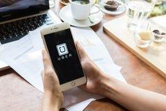 CHIANG MAI THAILAND - MAJ 09,2015: En kvinnahand som rymmer den Uber app visningen på iphone 6 plus i coffee shop, Uber är smartp Arkivbild