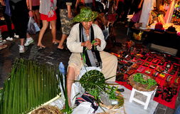 Chiang Mai, Thailand: Man Making Palm Frond Hats. A craftsman fashions hats out of palm fronds at the Sunday Walking Street Night Market on Thanon Ratchadamnoen Stock Images
