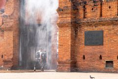 Tourists are walking through water spray installed at Thapae Gate. royalty free stock photography