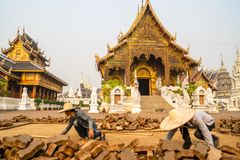 Chiang Mai/Thailand - March 16, 2019: Worker is paving the walkway with cobblestones in a Buddhist temple. royalty free stock images
