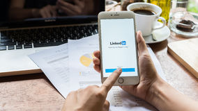CHIANG MAI, THAILAND 09 MEI 2016: Bedrijfsvrouw die een iPhone 6 plus met de sociale netwerkdienst LinkedIn houden op het scherm  Royalty-vrije Stock Afbeeldingen