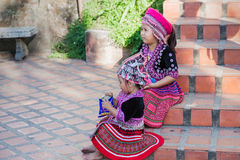Two Thai children in traditional clothes on the stairs to the Golden Temple of Chiang Mai. royalty free stock photo