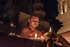 Monk handing over lamp to people after prayers, Chiang Mai, Thailand stock photos