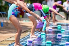 Young girl swimmers getting in position to jump into the swimming pool stock images