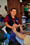 Chiang Mai, Thailand: Thai Masseur at Work. Thai masseur at work giving a traditional foot massage to a client at the Wat Sum Pao spa in Chiang Mai, Thailand stock photos