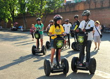 Chiang Mai, Thailand: Tourists Riding Segways. A group of young tourists riding Segway two-wheeled motorised vehicles in front of the old city walls near the Tha Stock Image