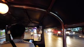 Chiang Mai, Thailand - 2019-03-15 - tuk tuk drives down street at night from view of driver stock video
