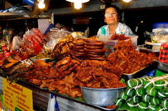 Chiang Mai, Thailand: Woman Selling Food. A tantalising array of foods including fried chicken and sausages can be found daily at the expansive Chiang Mai Gate Royalty Free Stock Photos