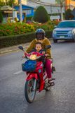 CHIANG RAI, ТАИЛАНД - 1-ОЕ ФЕВРАЛЯ 2018: Неопознанная женщина при ее сын используя предохранение от шлема и едущ a Стоковое Изображение