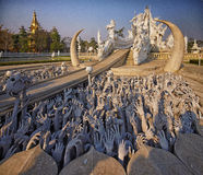 Chiang Rai Temple, Wat Rong Khun. Wat Rong Khun walkway to the temple that crosses in half  lake of stone hands Royalty Free Stock Image