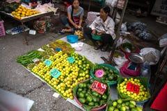 Chiang Rai Thailand - Augusti 04, 2016: Thailändska kvinnor som säljer exotiska frukter och grönsaker på gatamarknaden i Chiang R Arkivfoto