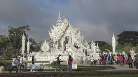 Chinese tourists at the entrance to the White temple Wat Rong Khun. Chiang Rai, Thailand. Chiang Rai, Thailand - December 16, 2018: Chinese tourists at the stock footage