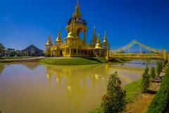 CHIANG RAI THAILAND - FEBRUARI 01, 2018: Härlig guld- tempel med en bro över en sjö, Wat Suan Dok kloster in Royaltyfri Bild