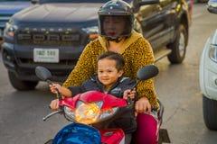 CHIANG RAI THAILAND - FEBRUARI 01, 2018: Oidentifierad kvinna med hennes son som använder ett hjälmskydd och rider a Royaltyfri Bild