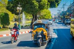 CHIANG RAI THAILAND - FEBRUARI 01, 2018: Utomhus- sikt av motorcykeln och några bilar som in parkeras i gatan i Chiang Mai Arkivfoto