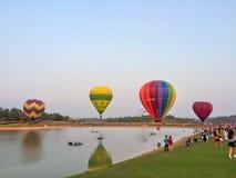 Chiang Rai, Thailand - February 14 2016: Colorful hot air balloon reflecting water and many people travel at Singha Park Chiang. Rai International Balloon stock photo