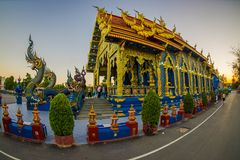 CHIANG RAI, THAILAND - FEBRUARY 01, 2018: Unidentified people at the enter, close to a dragon figure of Rong Sua Ten. Blue temple with blue sky un Chiang Rai Stock Images