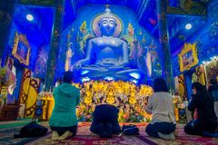 CHIANG RAJA TAJLANDIA, LUTY, - 01, 2018: Niezidentyfikowani ludzie ono modli się na ich kolanach przed ogromną Buddha statuą wewn Fotografia Royalty Free