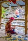 CHIANG RAJA TAJLANDIA, LUTY, - 01, 2018: Plenerowy widok niezidentyfikowany mężczyzna na jego kolanach z rybim jedzeniem w ich rę Obraz Royalty Free