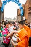 CHIANGMAI - 13 APRILE 2008: Il festival di Songkran, la gente ha messo le offerti dell'alimento nelle elemosine di un monaco budd Immagini Stock