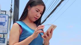 CHIANGMAI, THAILAND-MAY 6,2019: muchacha hermosa joven jugar un teléfono móvil en una parada y esperar de autobús el autobús almacen de metraje de vídeo
