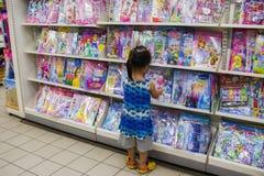 CHIANGMAI, THAILAND-MAY 3,2019: Piccolo bambino esplora gli scaffali per libri nel deposito di libro fotografie stock libere da diritti