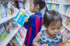 CHIANGMAI, THAILAND-MAY 3,2019: Poco niño explora los estantes con la mamá en librería foto de archivo libre de regalías