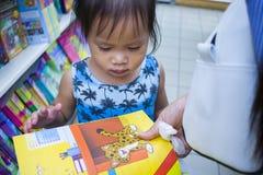 CHIANGMAI, THAILAND-MAY 3,2019: Poco ni?o explora los estantes con la mam? en librer?a fotografía de archivo libre de regalías