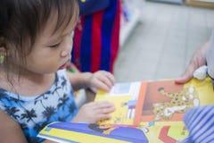 CHIANGMAI, THAILAND-MAY 3,2019: Poco ni?o explora los estantes con la mam? en librer?a fotos de archivo libres de regalías