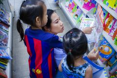 CHIANGMAI, THAILAND-MAY 3,2019: Wenig Kind erforscht die B?cherregale mit Mutter im Buchladen lizenzfreie stockfotografie