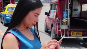 CHIANGMAI,THAILAND-MAY 6,2019 :  young beautiful girl play a mobile phone at a bus stop and waiting for the bus. High resolution image gallery stock video footage