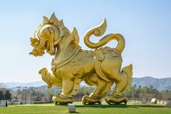The statue of golden lion on a field with blue sky background, at Singha park Chiangrai stock photography