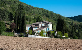 Chianti house with cyan windows. With a plowed field in foreground and woods hills in the background Stock Photo