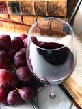 Chianti reserve red wine, glass, grapes. Chianti reserve wine, glass, grapes and old books Stock Image