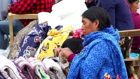 Indigenous woman weaving a sweater to sell. CHIAPAS, MEXICO-CIRCA AUGUST 2018: Indigenous woman weaving a sweater to sell in the public square in San Cristobal stock footage