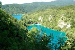 Chiara acqua blu e parco nazionale verde dei laghi Plitvice della foresta fotografie stock
