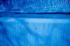 Chiara acqua della luce intensa che scorre verticalmente primo piano del fondo Fotografie Stock
