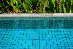 Chiara acqua della piscina che mostra il quadrato dell'argilla del blu di turchese fino a Fotografie Stock