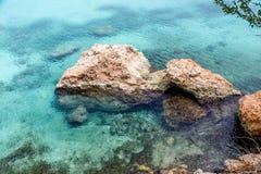 Chiara Aqua Water Around Rocks immagine stock libera da diritti