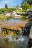 Chiari chiari scorrimenti dell'acqua dalle pietre che le lavano e che le puliscono Il cielo e gli alberi circostanti sono rifless fotografia stock libera da diritti