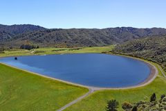 Chiaro bacino idrico blu messo nelle colline in isola del nord, Nuova Zelanda fotografie stock libere da diritti