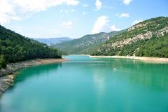 Chiaro lago blu fra i pendii Fotografie Stock