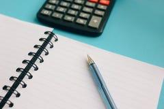 chiaro taccuino, penna e un calcolatore su un fondo blu immagini stock libere da diritti