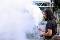 Chiarore del fumo della tenuta dell'uomo Immagine Stock Libera da Diritti
